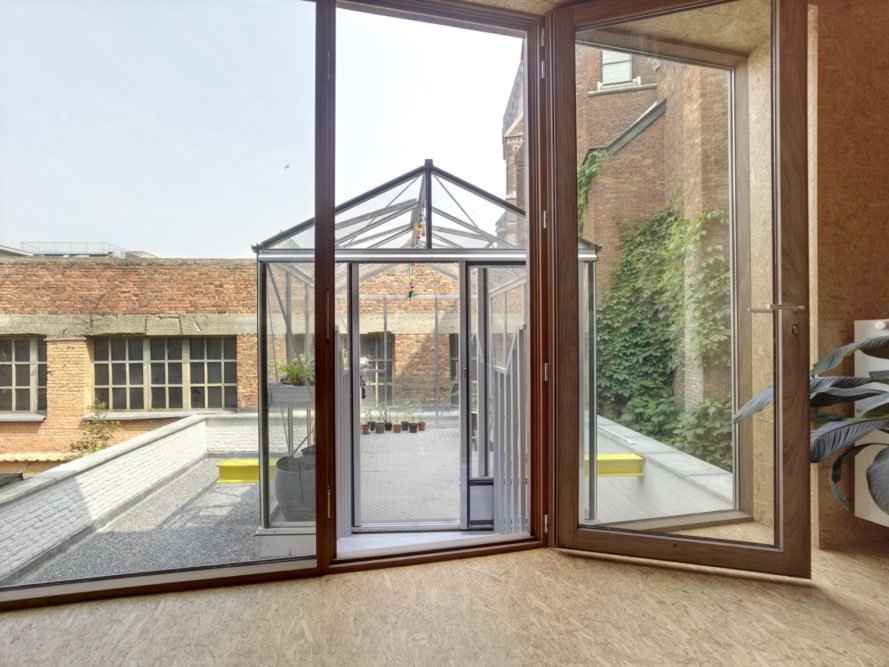 wood room and wood-framed door leading to outdoor greenhouse