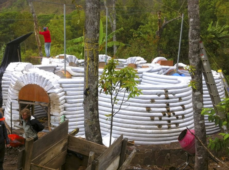 white domes under construction with peace sign on one curved wall