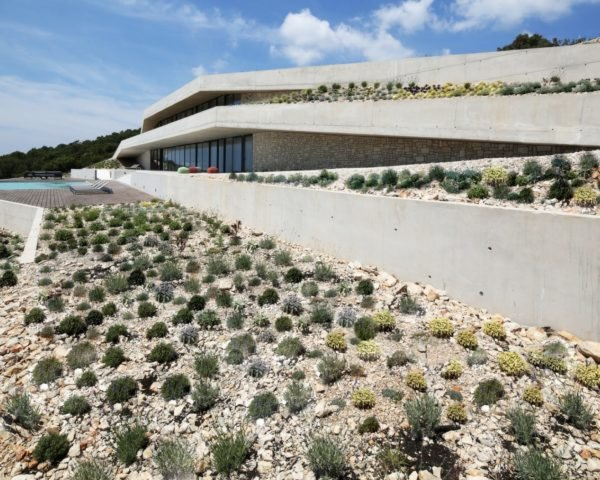concrete home with rocky, desert-planted green roof