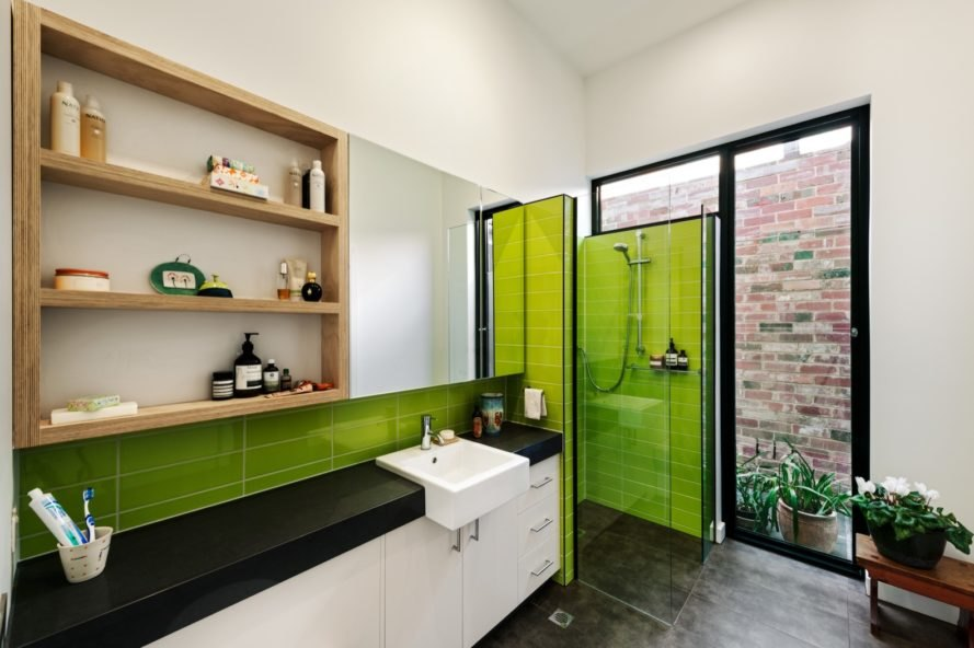 white bathroom with small area of green tile and green glass walls around the shower