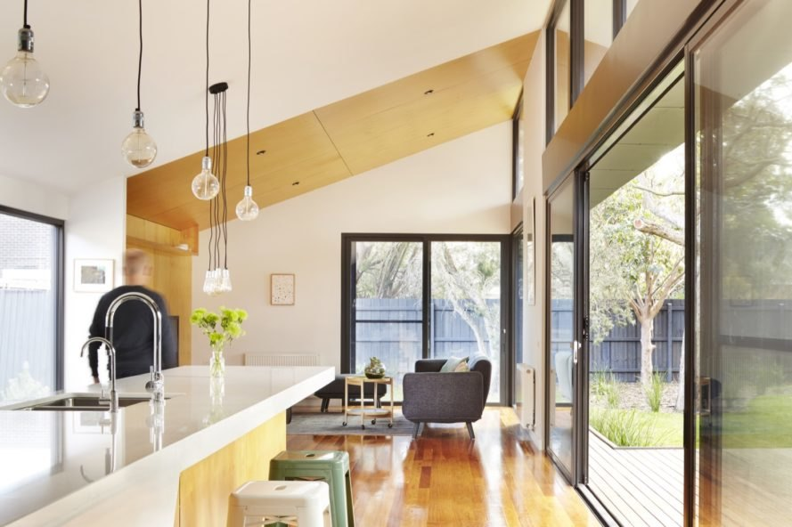 open-plan living room and kitchen with white walls and cabinets, wood floors, a gray couch and several large windows