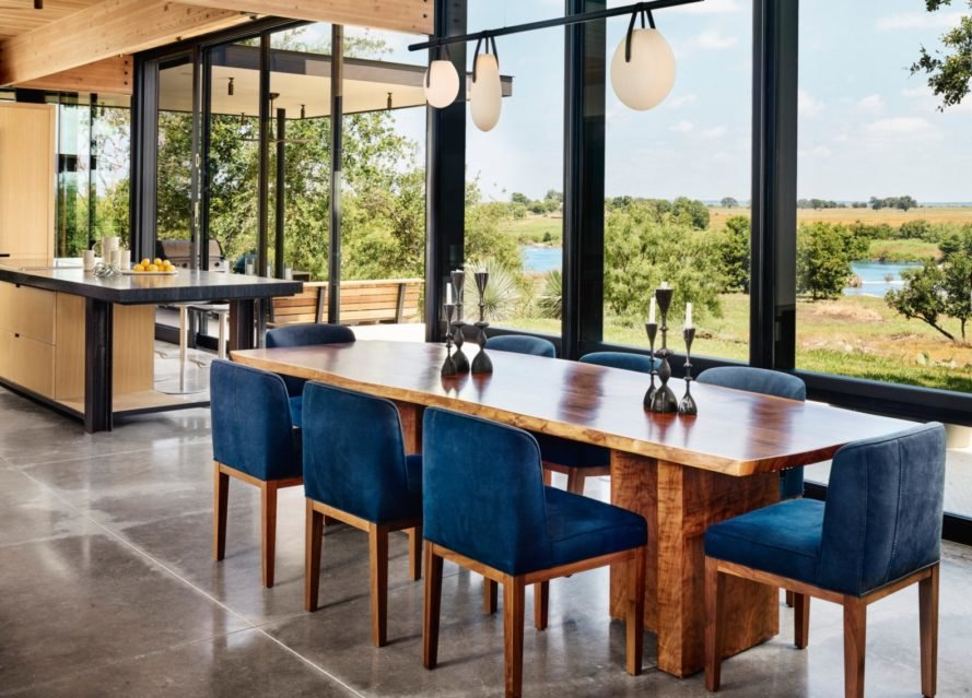 a large wooden dining table with blue seats