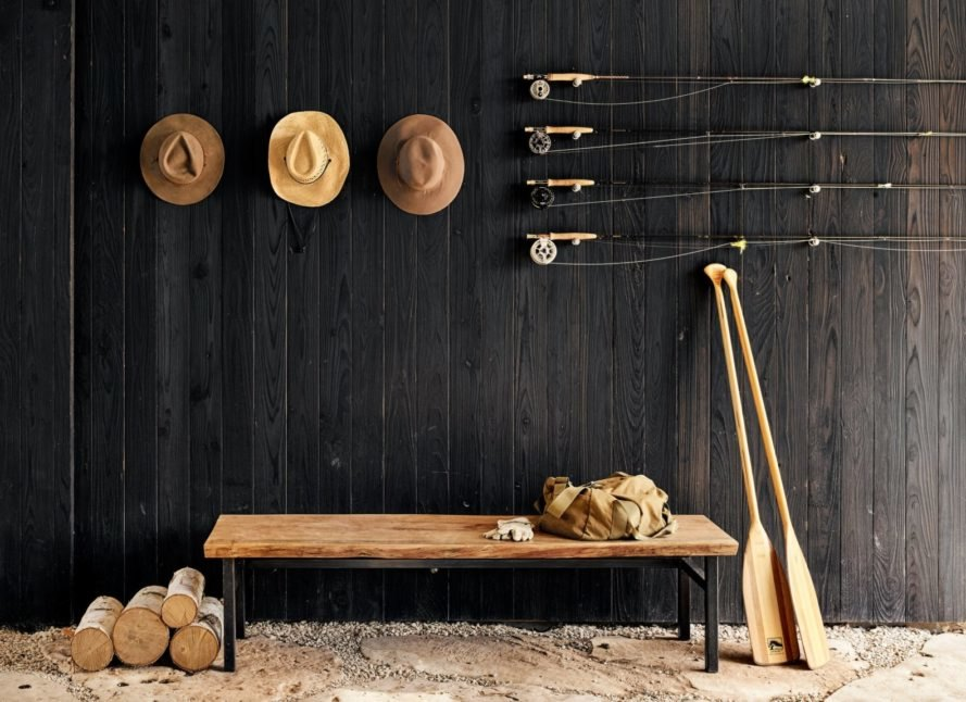 a charred wood wall with hats and walking sticks
