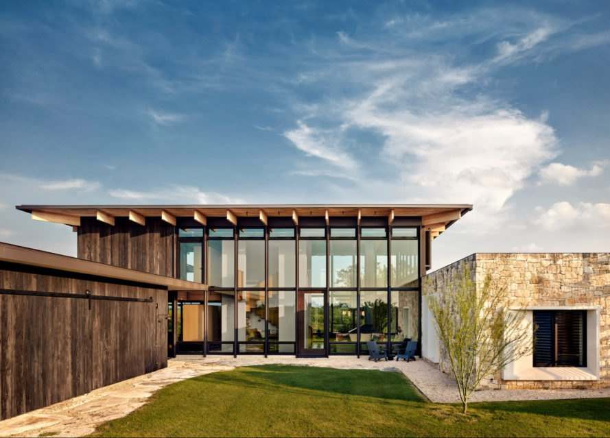 a glass and wooden home with flat roof