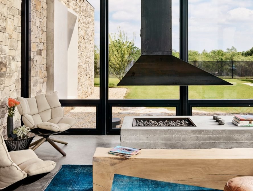 a living space with seating area, hanging fireplace