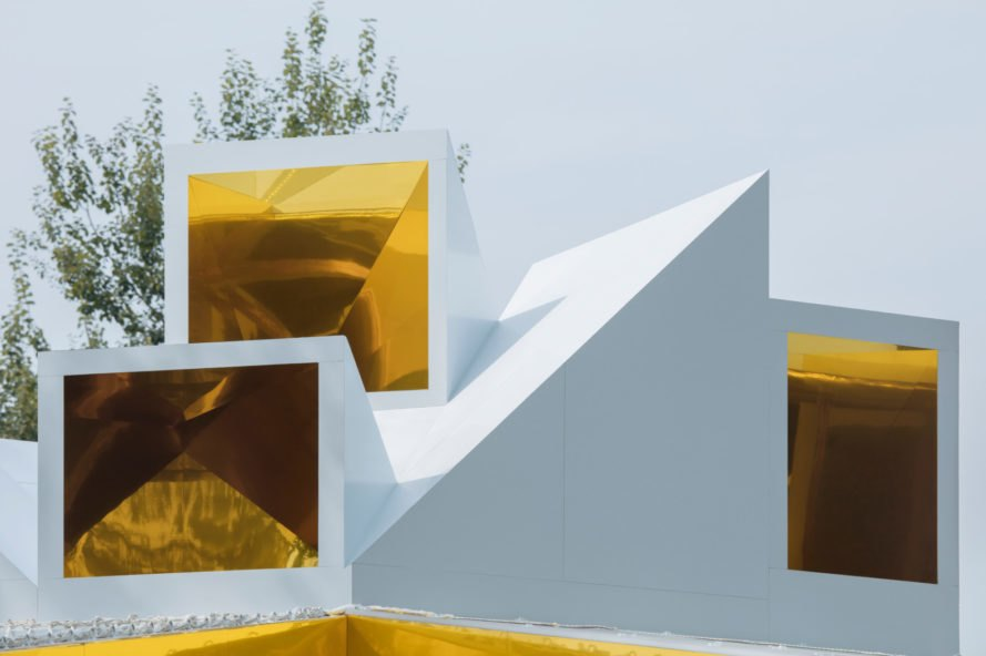 white building with geometric gold cut outs on the roof