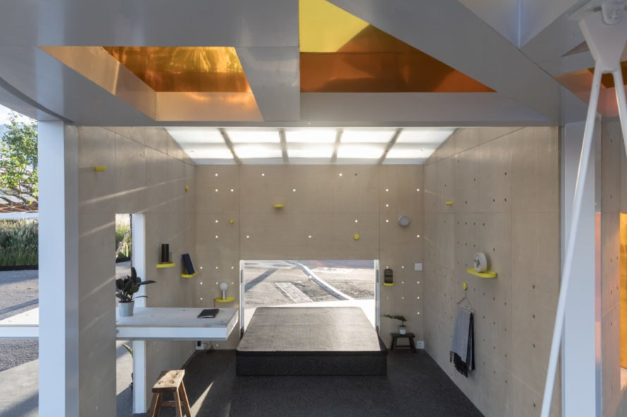living area with white walls and gold cut outs in the ceiling