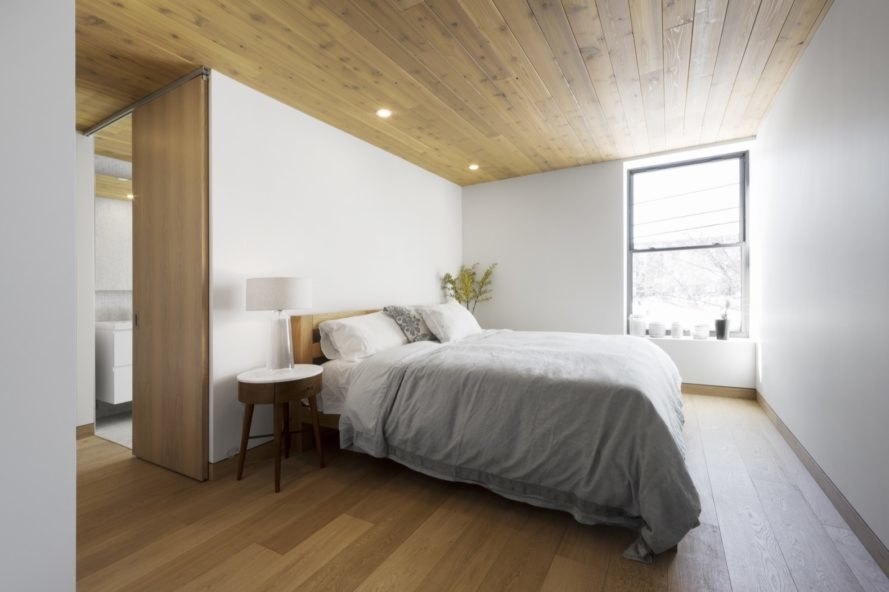 white bedroom with wood ceilings and floors and bed with gray bedding