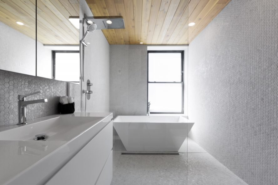 bathroom with white penny tiles on walls and floor
