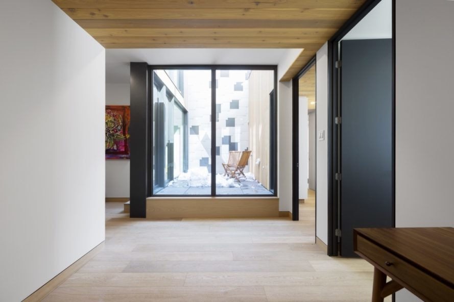 white hallway with black doors and black-framed windows