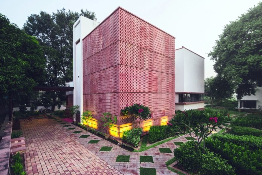 perforated brick home surrounded by green plants