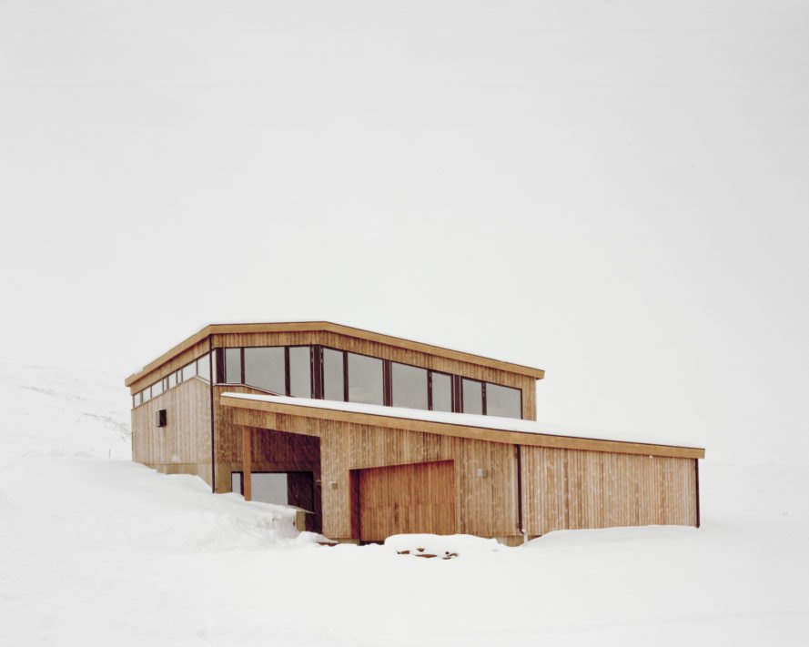 a light wood cabin on snowy hill