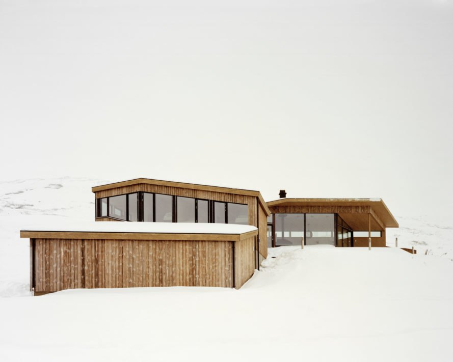 a light wood cabin with glass walls