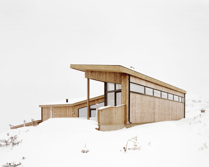 light wood cabin with slanted roof on snowy landscape