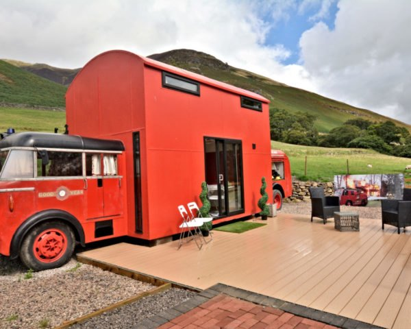 red fire truck converted into a tiny home with deck