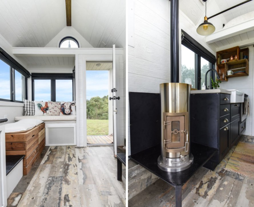 interior of tiny home with white walls, wooden floors and a small wood-burning stove