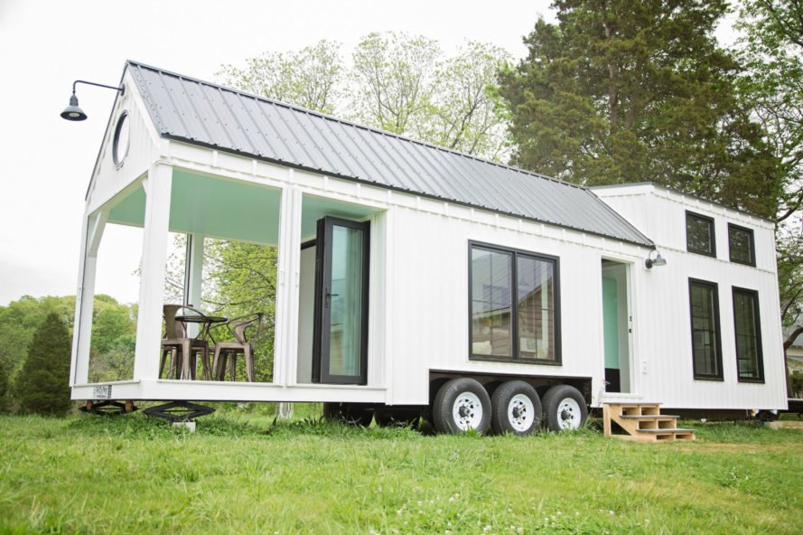 white tiny home with large covered porch