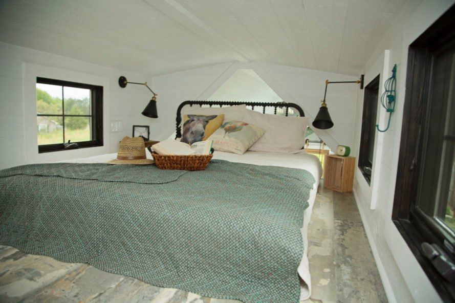 bed with gray comforter in tiny room