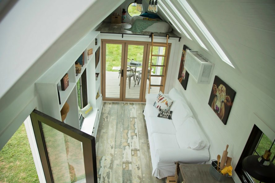 aerial view of white living space with white couch and cow artwork on the walls