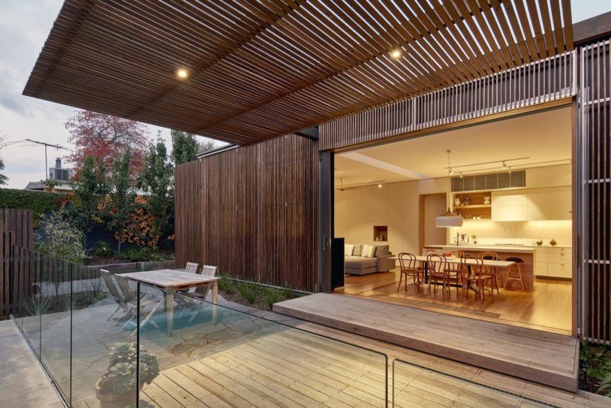 wooden outdoor deck with a light wood table under a large timber screen