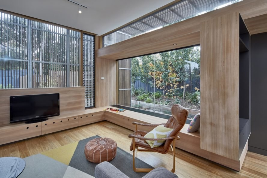 living area with timber and glass walls and tan leather seat
