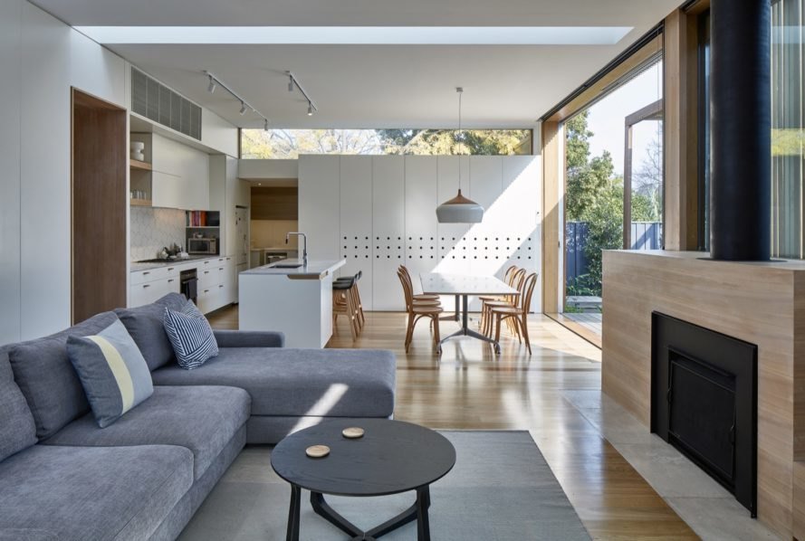 gray sectional sofa facing a fireplace with dining table and white kitchen in background