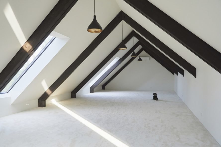 attic with white walls and floors and exposed wood ceiling beams