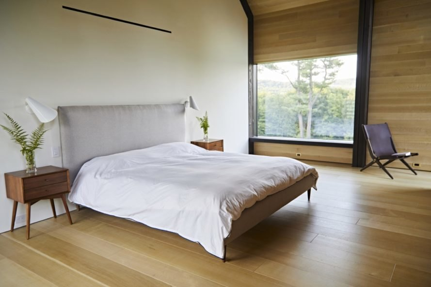 bedroom with timber walls and floors and large window