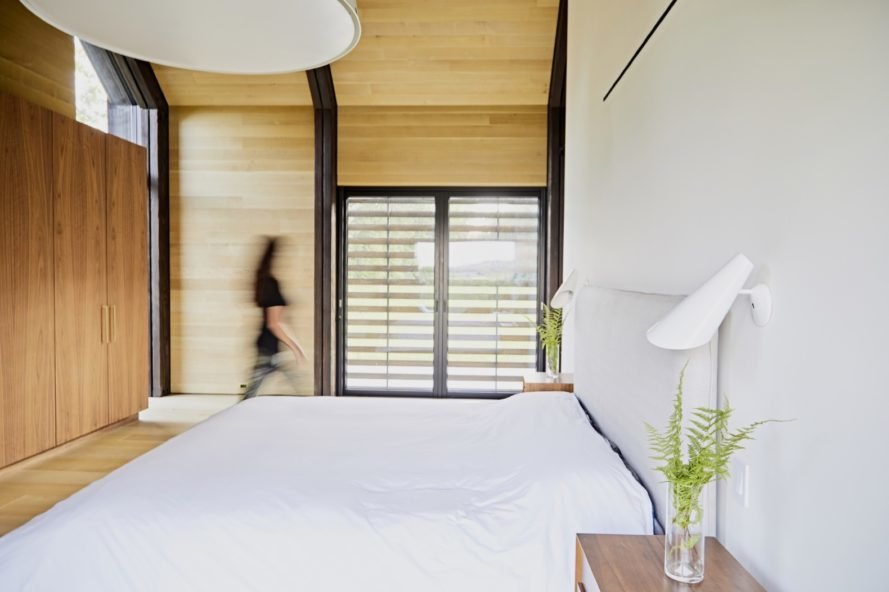 bedroom with timber walls and floors and white bedding