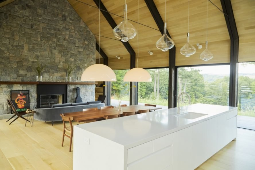 open plan kitchen, living and dining area with white kitchen island and timber ceilings