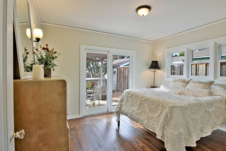 bedroom with white bed and large glass door