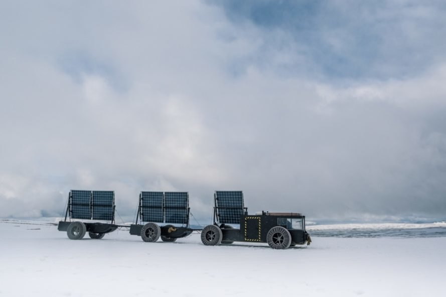 black solar-powered vehicle driving on snowy landscape