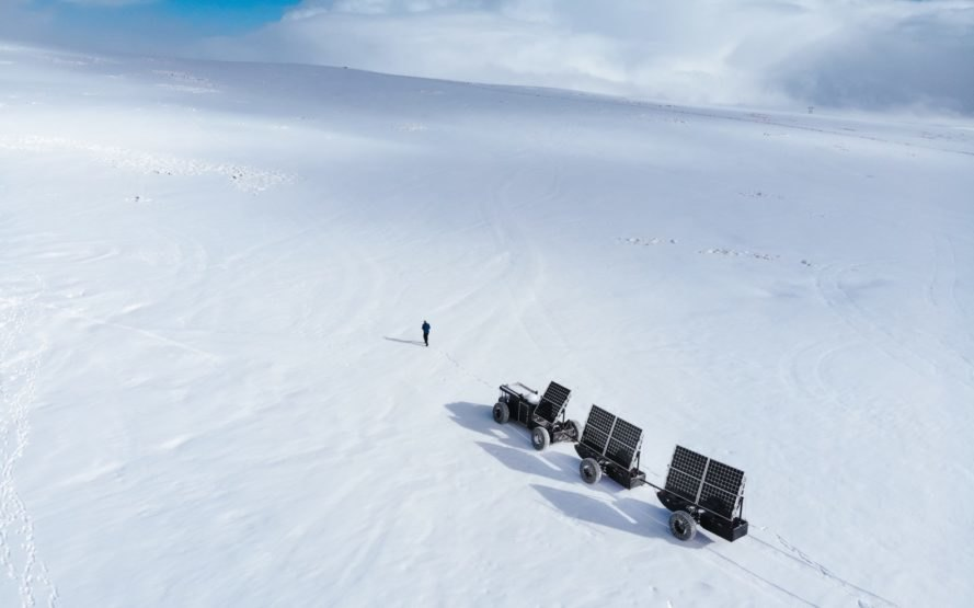 person walking near black solar-powered vehicle on snowy landscape