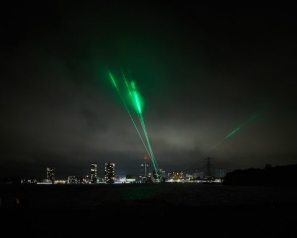 green laser lights above a city skyline
