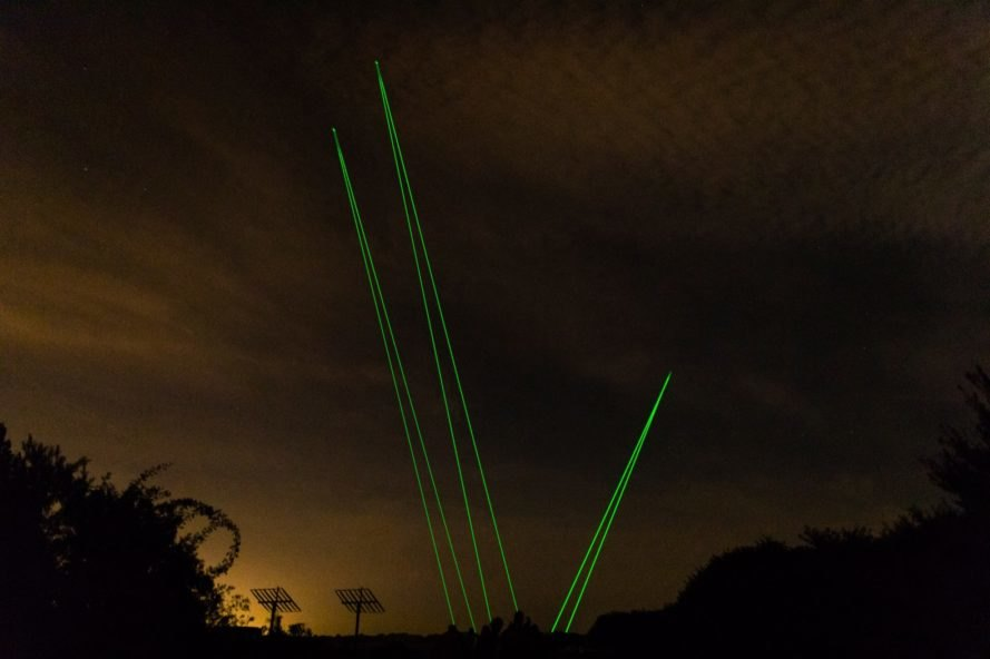 green laser lights in a dark sky
