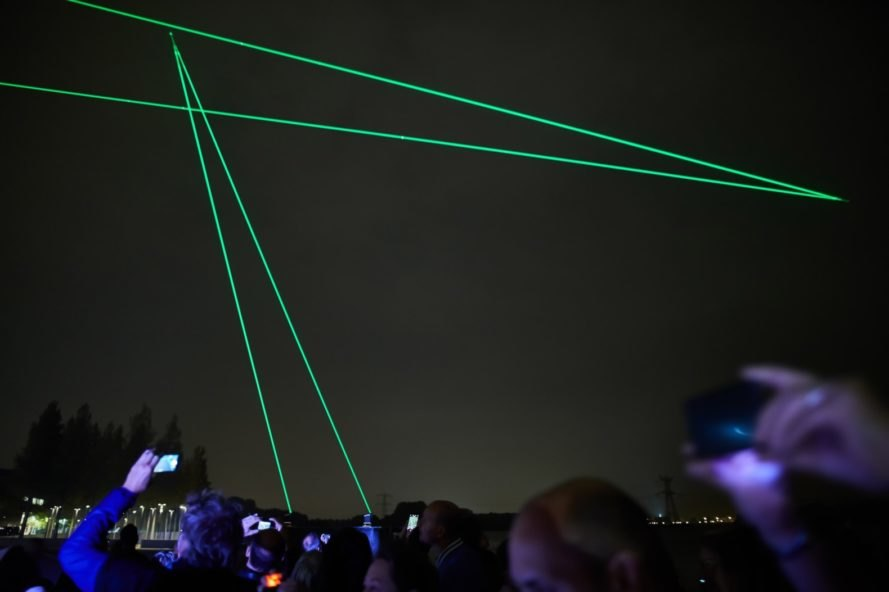 crowd looking up at green laser lights in dark sky