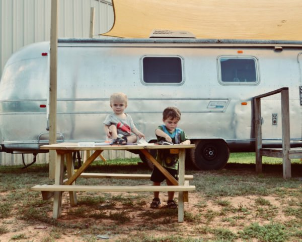 two kids on a picnic table in front of an airstream