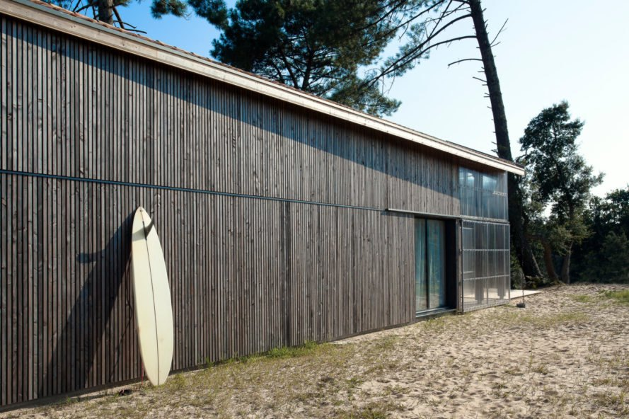 elongated home with surf board resting against the exterior