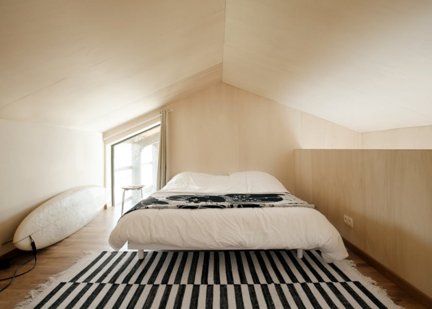 bedroom with natural wood paneling and striped rug