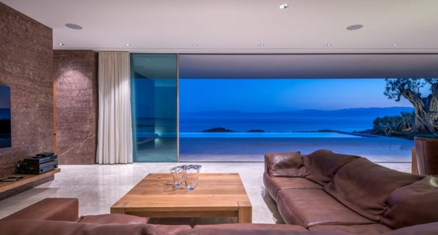 brown couches facing wall of glass exposing views of sea