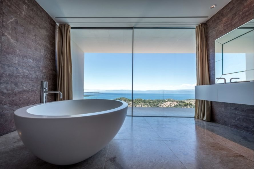 large round bathtub facing glass wall with sea views
