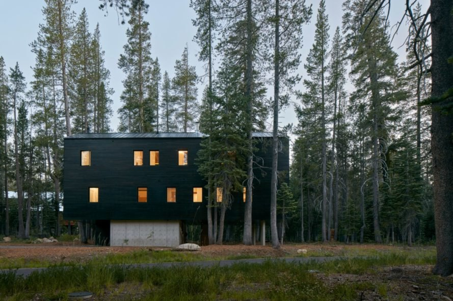 large black home with several windows lit up at dusk in forestscape