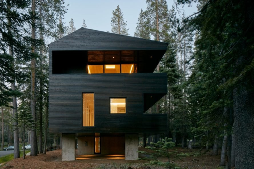 elevated black home with several windows in forestscape
