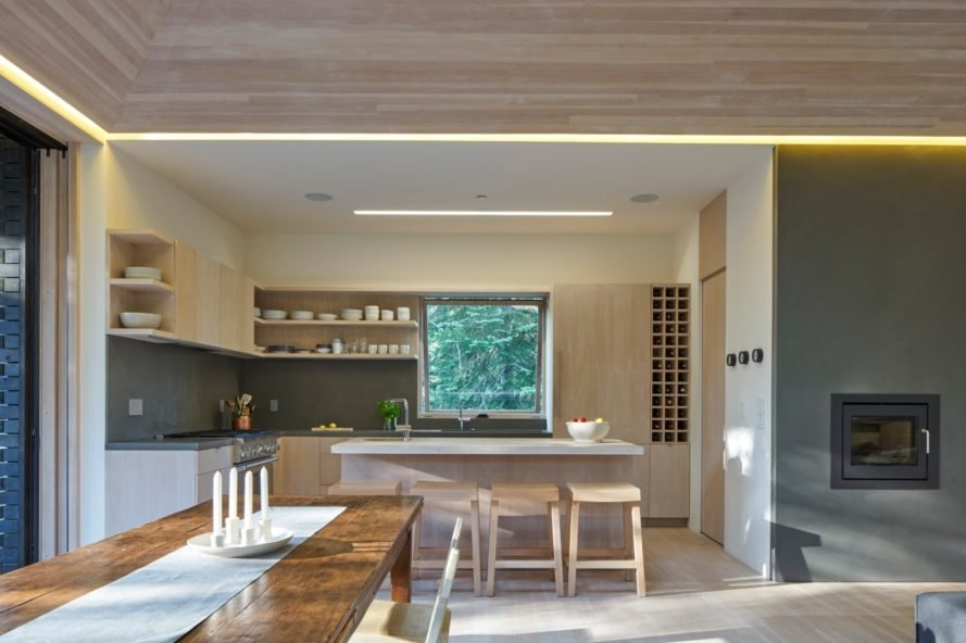 a kitchen with light wood cabinetry in the background with a wood dining table in foreground