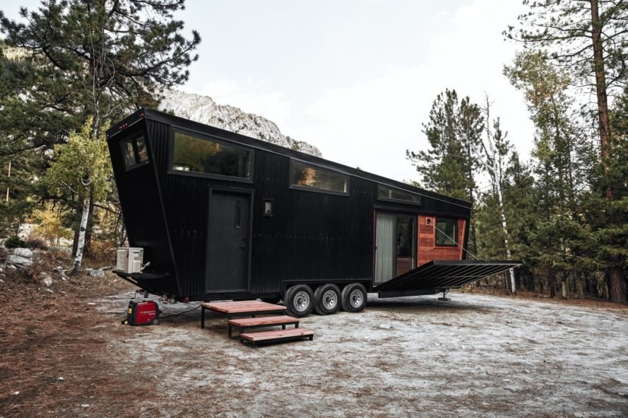 black RV with slanted roof and a front deck