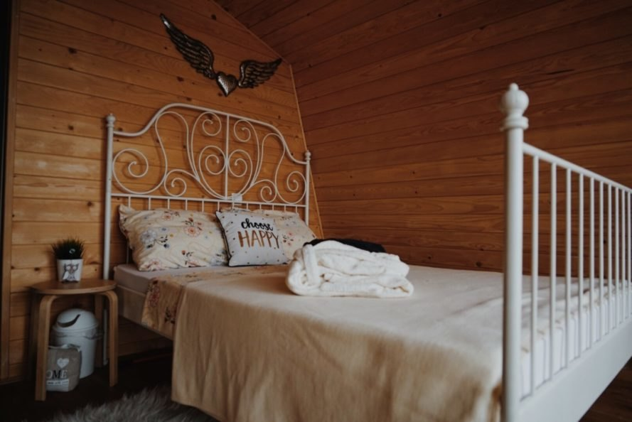 a wood-lined bedroom with white bedding