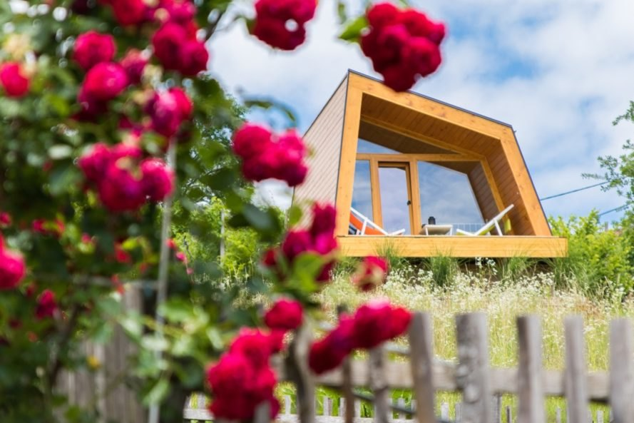 geometric cabin with front deck and pink flowers in foreground