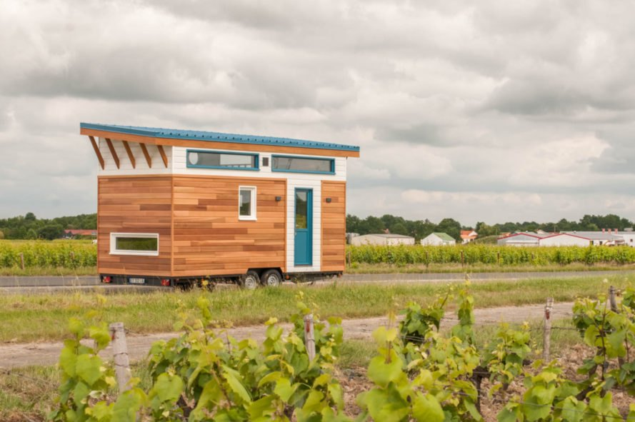 tiny home clad in cedar panels with white trim and teal front door