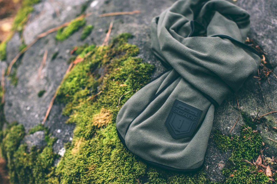 olive green scarf on top of a moss-covered rock