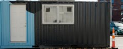 blue and black shipping container with window and white door